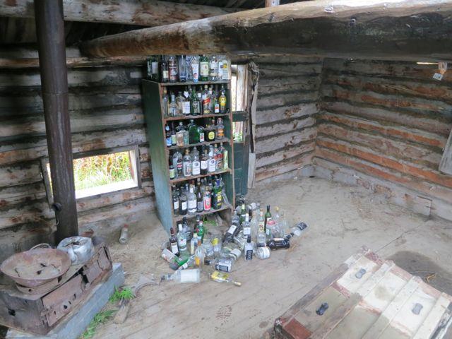 Kanada: Schnapsflaschen in alter Hütte im Big Salmon River